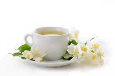 Cha branco em xicara com pires e flores