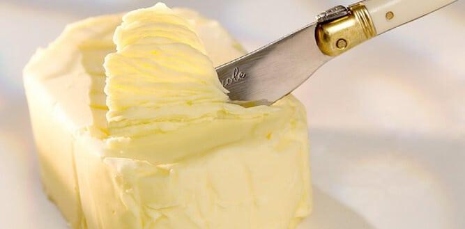 manteiga deliciosa sendo retirada com uma faca